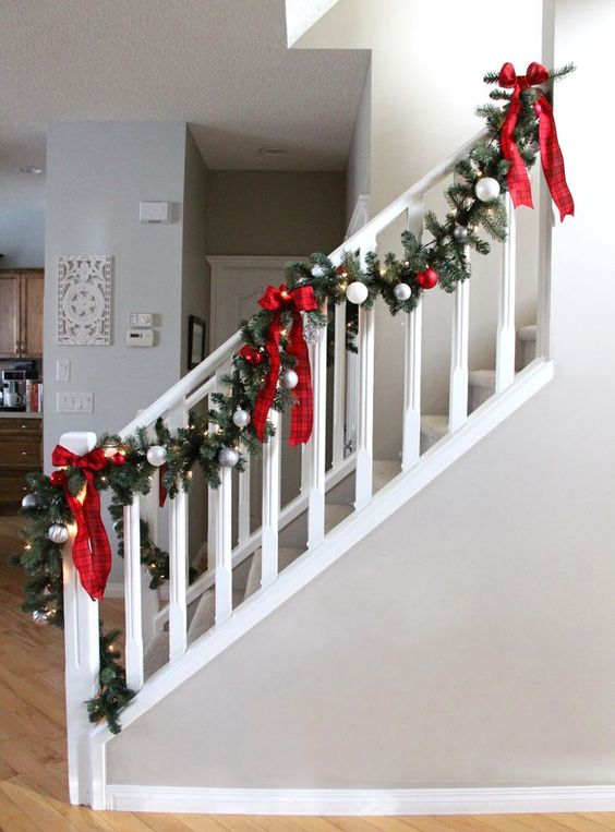 a pretty fir garland with silver and red ornaments, lights and plaid bows is a lovely and bold decor idea for Christmas