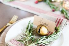 a pretty rustic Christmas place setting with a plaid napkin, greenery, a gold bell holding a card is very chic
