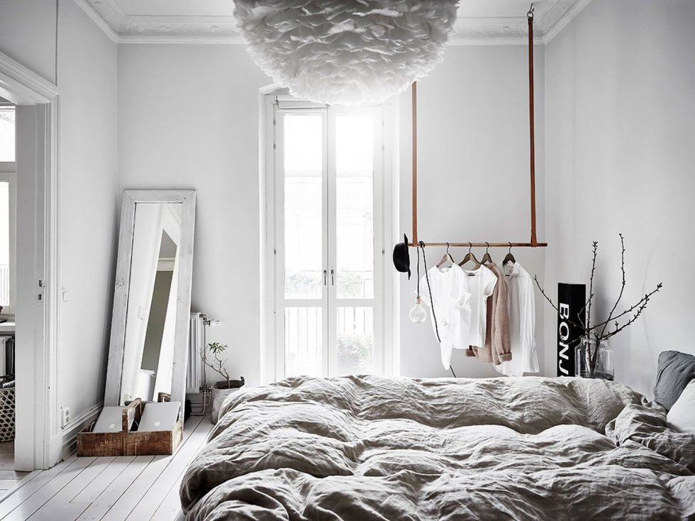 a quirky and airy Scandinavian bedroom with a mirror in a frame, railing for clothes, a paper ruffle lamp and grey bedding