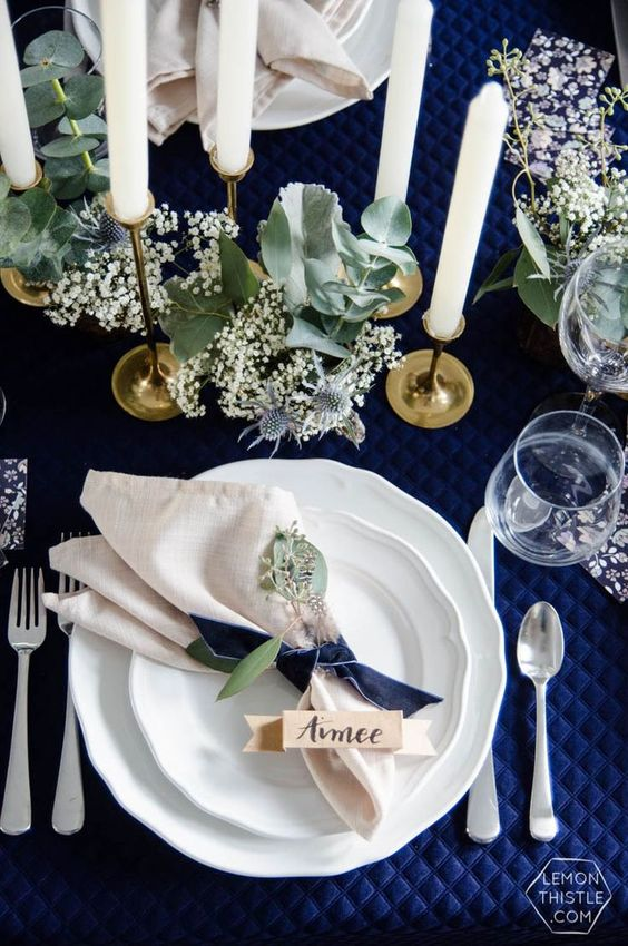a refined Christmas tablescape with a navy tablecloth and bows, neutral napkins, greenery and white candles is a chic idea