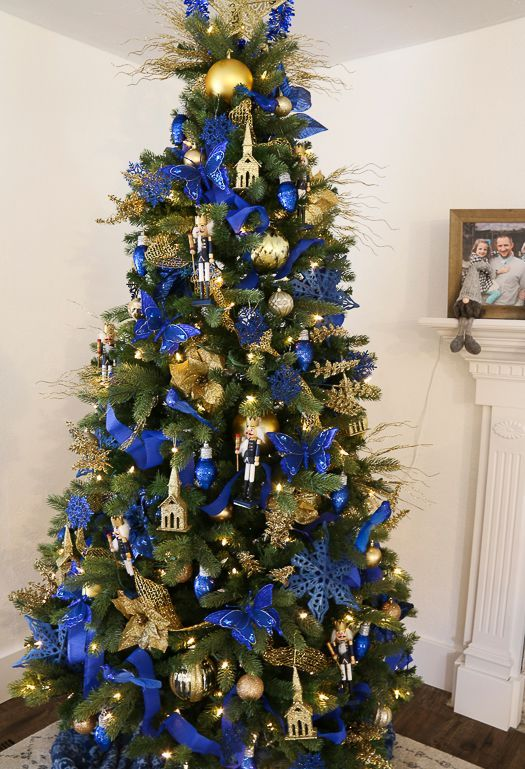 a refined and bold Christmas tree with lights electric blue and gold ornaments, butterflies fabric and paper blooms