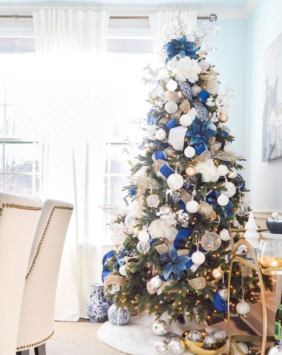 a refined and chic Christmas tree with lights, white and gold ornaments, fabric blooms and ribbons and twigs and branches