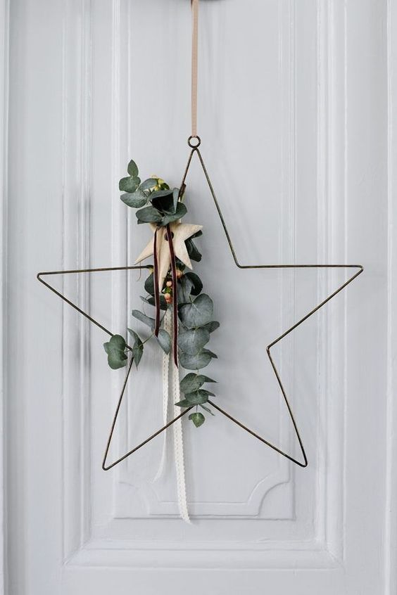 a refined star-shaped wreath with eucalyptus, a wooden star and leather cords is a nice alternative to a usual Christmas wreath