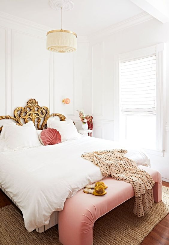 a refined vintage bedroom with a gorgeous bed with a gilded headboard, a pink curved bench, a fringe chandelier and pink linens is wow