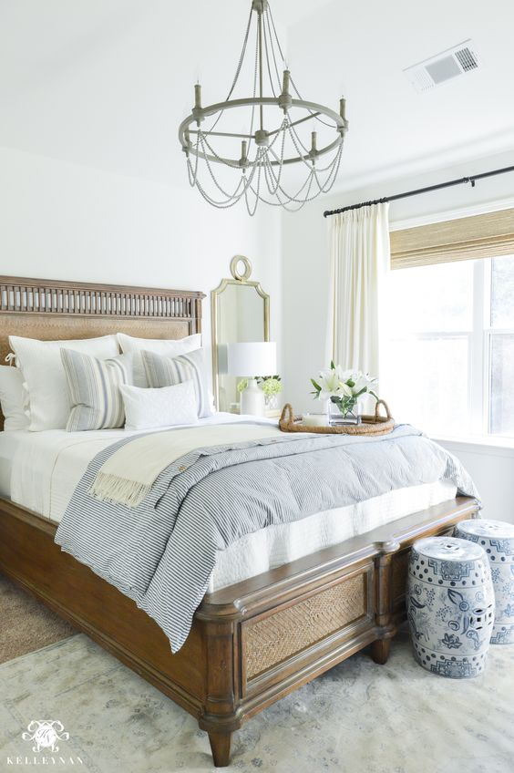 a refined vintage bedroom with a heavy wooden bed, a vintage chandelier, mirrors, baskets and neutral and printed textiles