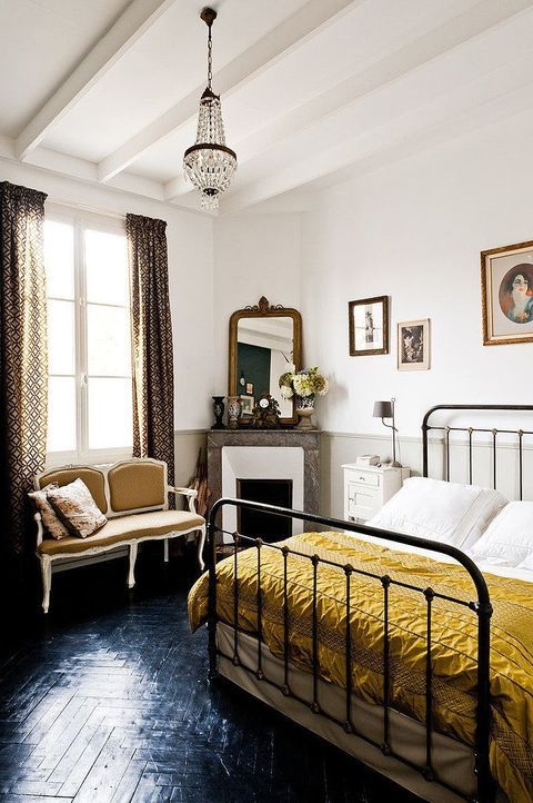a refined vintage bedroom with a metal bed, a pretty loveseat by the fireplace, a crystal chandelier and some artworks