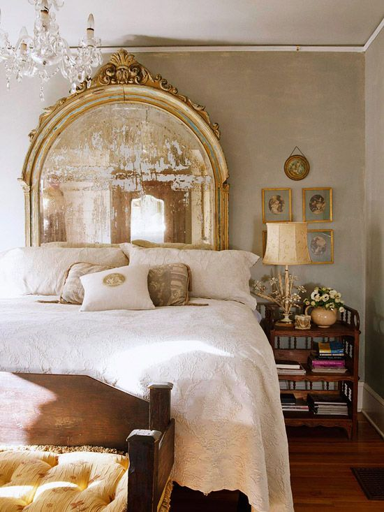 a refined vintage bedroom with an oversized mirror, a crystal chandelier, vintage furniture and artworks is pure chic
