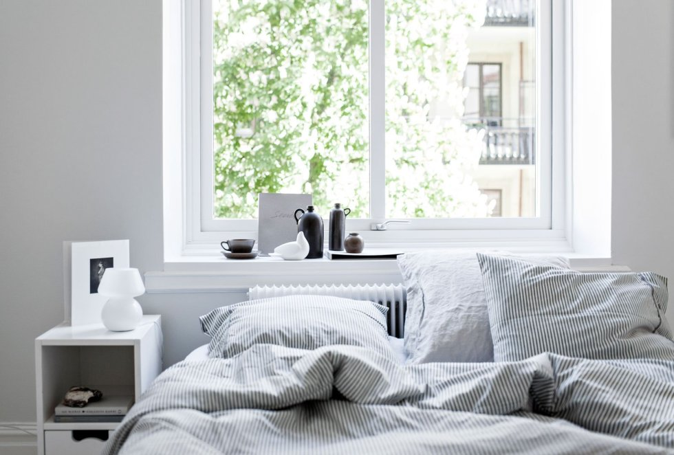 a relaxing Scandinavian sleeping space with white furniture, black vases, a bed with striped bedding