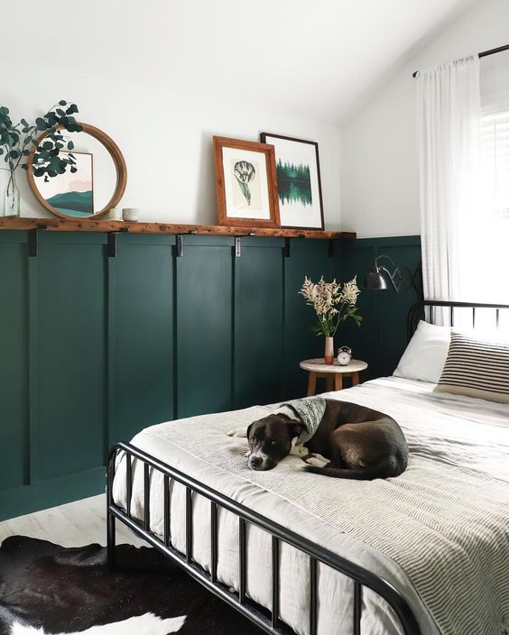 a retro bedroom with green wall panels, a metal bed, neutral bedding, a rough wooden shelf, artworks and a mirror