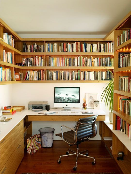a retro home office with a floating desk, an oversized bookshelf unit, a leather chair and some greenery is welcoming