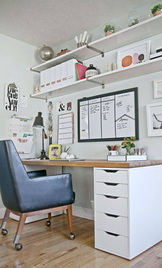 a retro home office with open shelves, a desk, a black leather chair, lots of memo boards and potted plants on the shelves