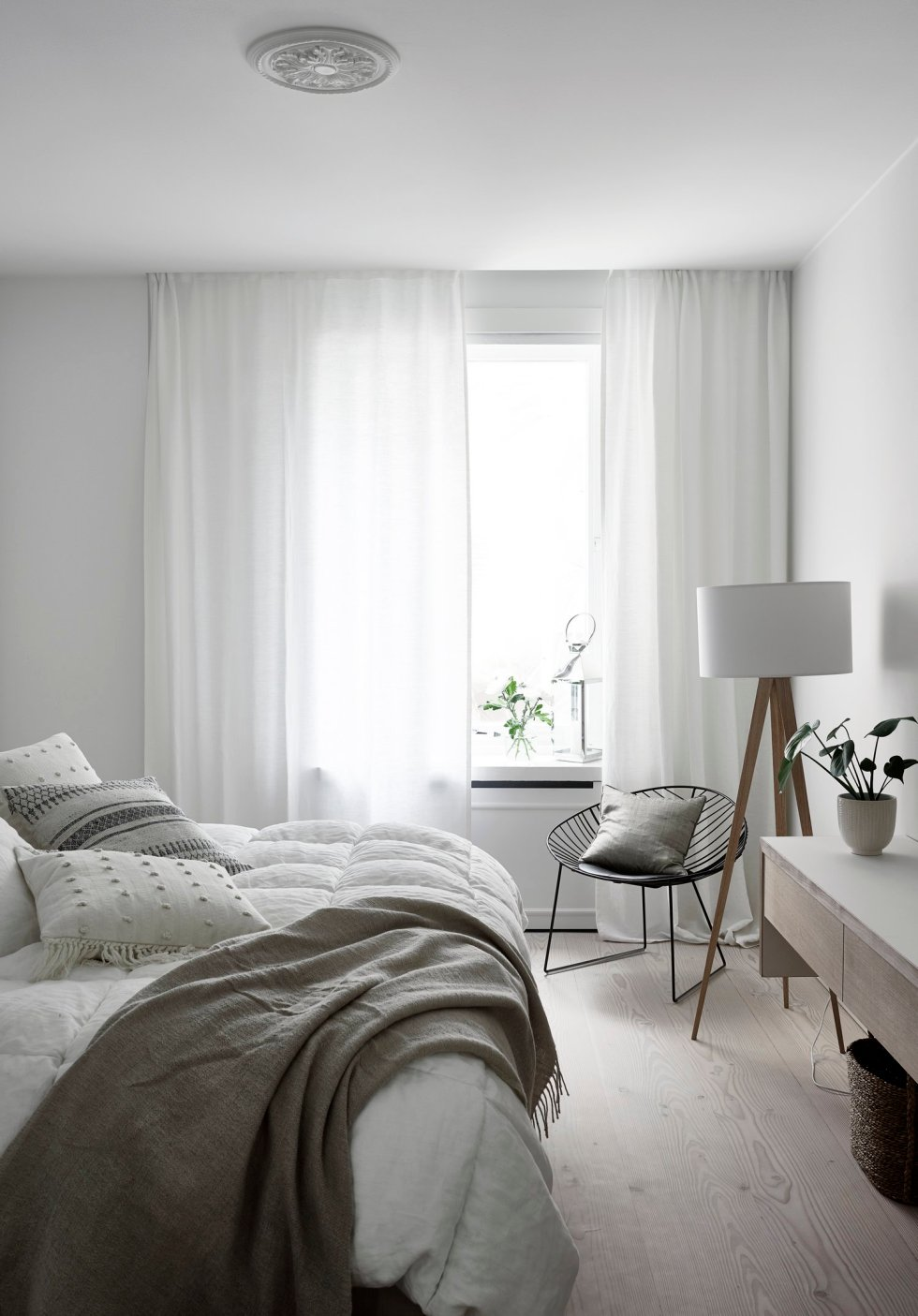 a serene and clean Scandinavian bedroom with stylish furniture, a floor lamp, a black chair and neutral bedding