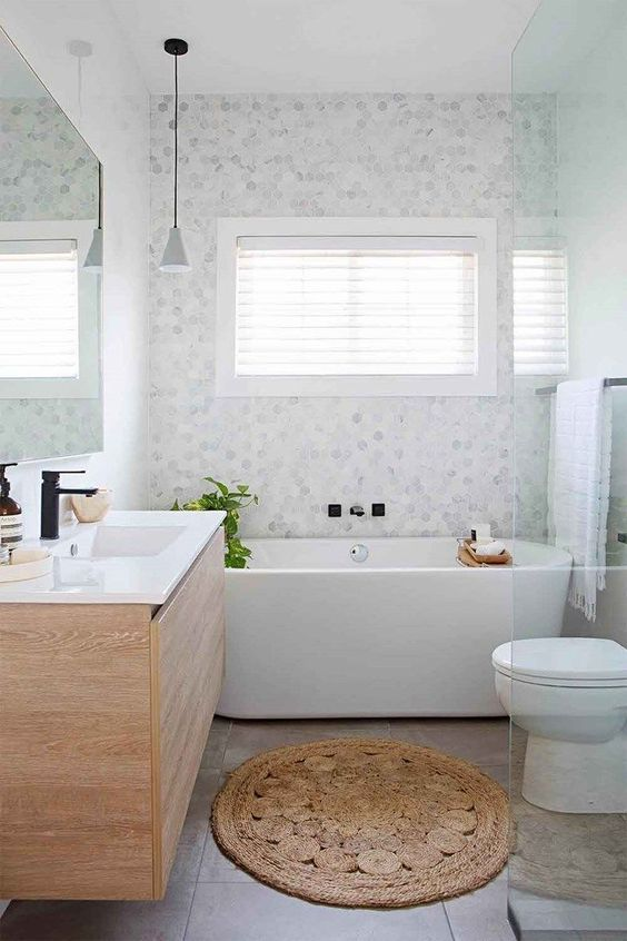 a serene bathroom with marble hex tiles and large scale ones, a wooden vanity and a bathtub plus a shower space