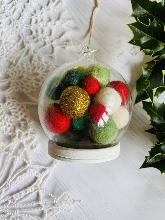 a sheer glass ornament with colorful pompoms inside is a very creative and bright decoration for winter holidays