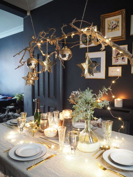 a shiny and glam Christmas tablescape with lights, gold cutlery, a branche with lights and ornaments, greenery, stars and glasses