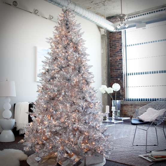 a shiny silver Christmas tree with lights is a glam and bright idea, it looks very stylish and modern, no additional decor required