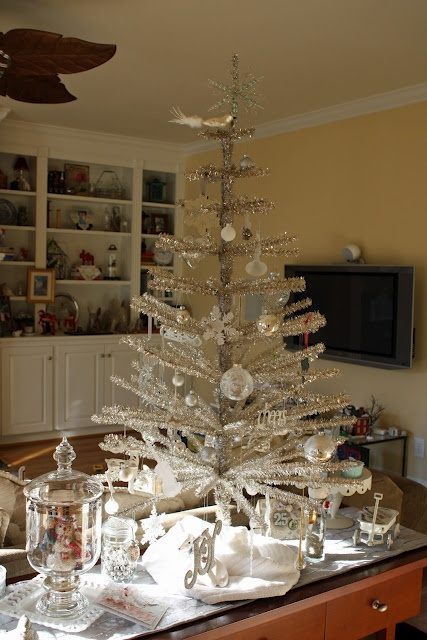 a shiny silver Christmas tree with white and silver ball and snowflake ornaments can be a nice tabletop decoration or an additional tree in some room