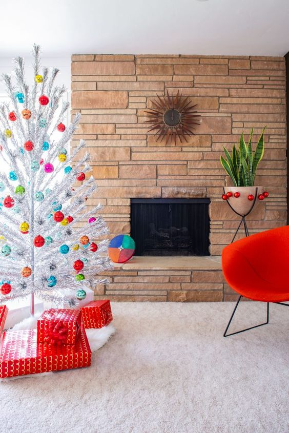 a silver Christmas tree with colorful ornaments and stacks of red gift boxes for a mid-century modern space