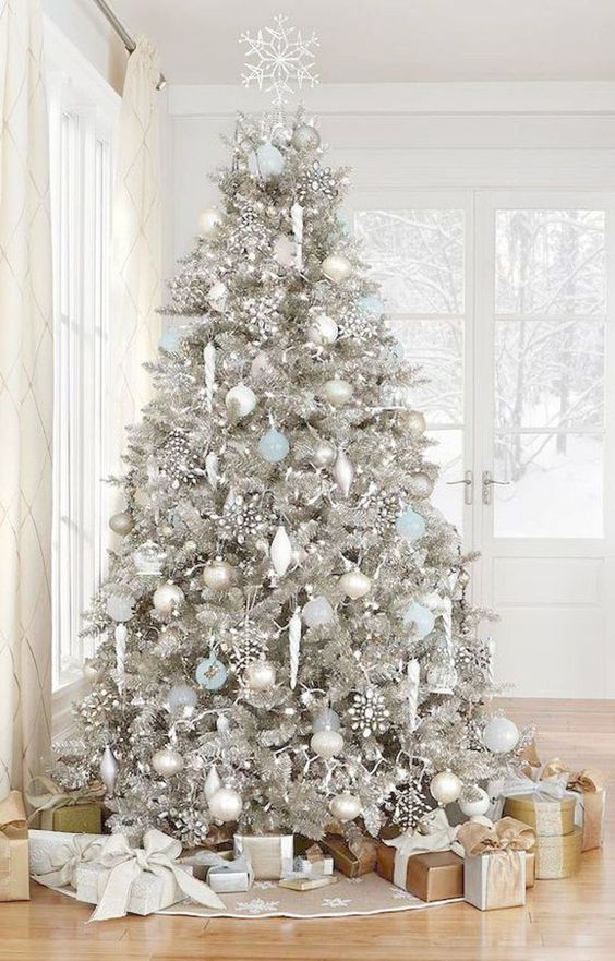 a silver Christmas tree with white, silver and blue ornaments, rhinestone snowlakes and some lights feels frozen
