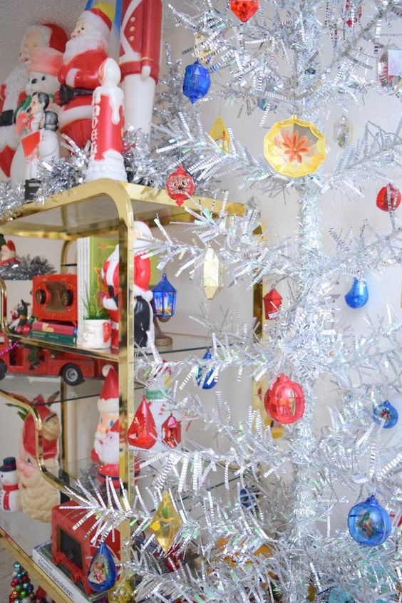 a silver mid-century modern Christmas tree with yellow, blue and red ornaments is a bold and catchy idea for retro fans