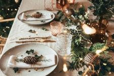 a simple Christmas setting with a fir branch runner, lights, candles, catchy glasses, pinecones, greenery and printed porcelain