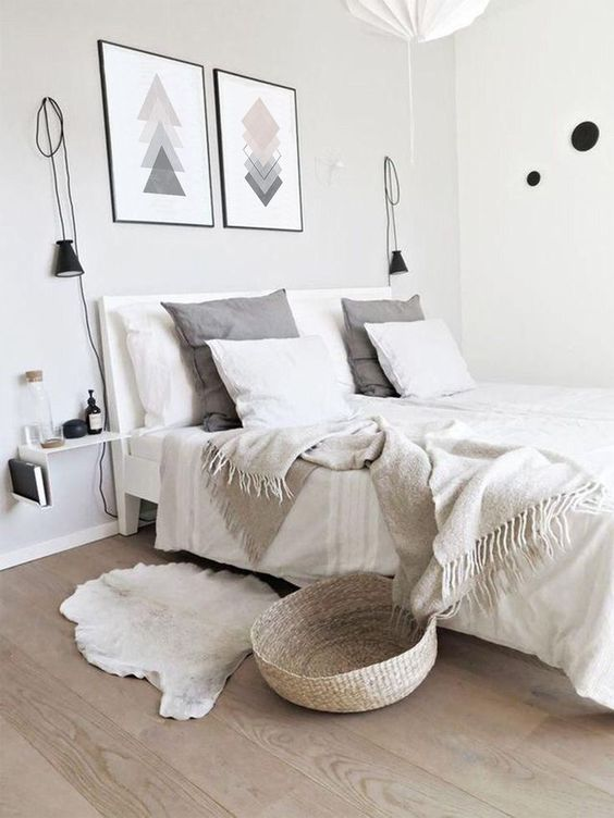 a simple Scandinavian bedroom with a white bed, neutral bedding, geometric artworks, sconces, a floating nightstand and a basket