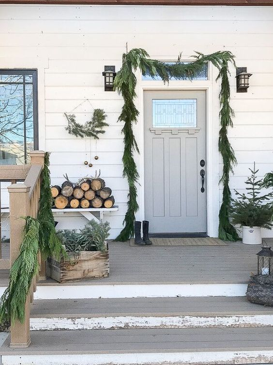 a simple and rustic Scandinavian Christmas porch with a fir garland, potted trees, a wreath with bells, firewood and crates with greenery