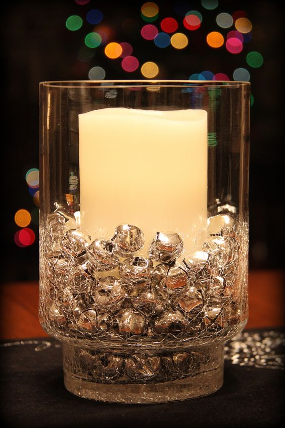 a simple holiday decoration or centerpiece of a glass with a single candle and lots of silver bells cna be made last minute