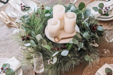 a simple yet glam Christmas tablescape with a greenery and berri wreath wrapping candles, woven chargers, gold cutlery and leaves
