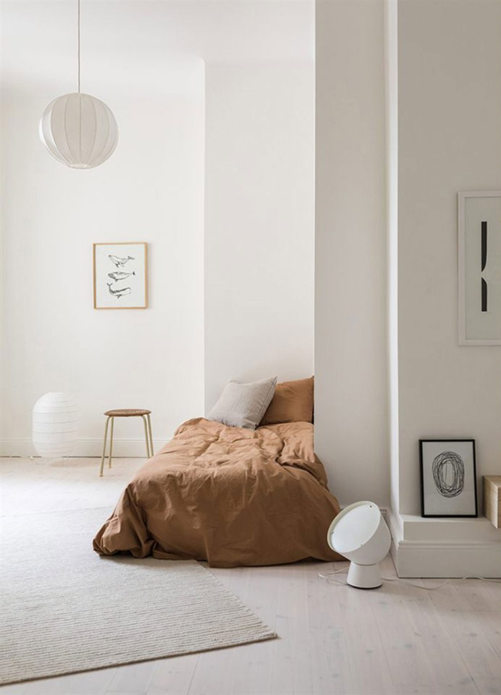 a simplistic Scandinavian bedroom with a low corner bed, a stool, some art and paper lamps feels airy and serene