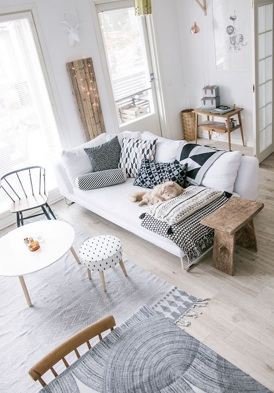 a small Nordic living room with a white sofa, black and white pillows, mismatching chairs and stools, some lights and blankets is cool