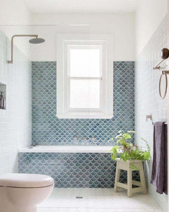 a small and chic bathroom with a shower space and a bathtub clad with blue scallop tiles plus a potted plant