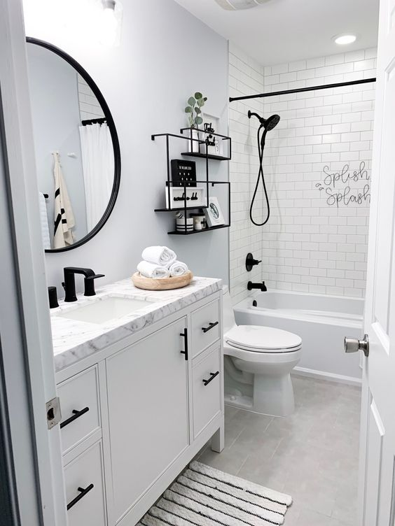a small and cool bathroom clad with neutral tiles, with a grey accent wall, black shelves and fixtures, black frames for an accent and more interest