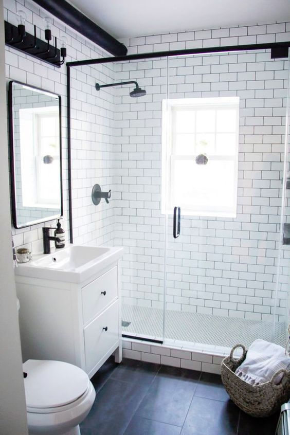 a small and cool bathroom with white subway tiles, black ones on the door, a shower space and touches of black here and there