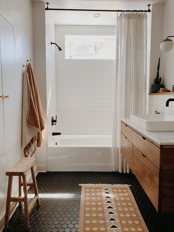 a small and cozy bathroon done with white subway and black hex tiles, a wooden vanity, neutral linens and a wooden stool