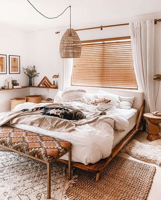 a small and neutral boho bedroom with wooden furniture, a boho bench, a wicker lamp, baskets for storage and artworks