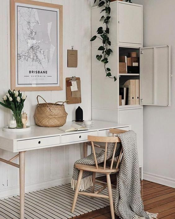 a small and neutral work space with a sleek desk, a wooden chair, a small vertaical cabinet for files and documents and some art