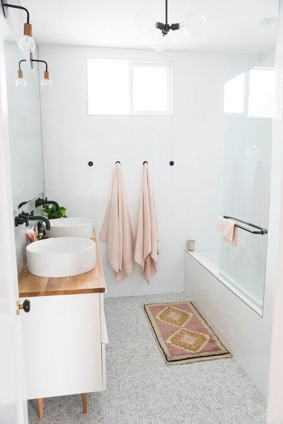 a small and welcoming bathroom clad with neutral tiles, a vanity with a wooden countertop, a bathtub and a chandelier