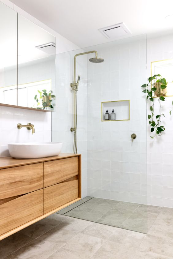 a small and welcoming modern bathroom with white and grey tiles, a catchy wooden vanity, a mirror cabinet and touches of brass