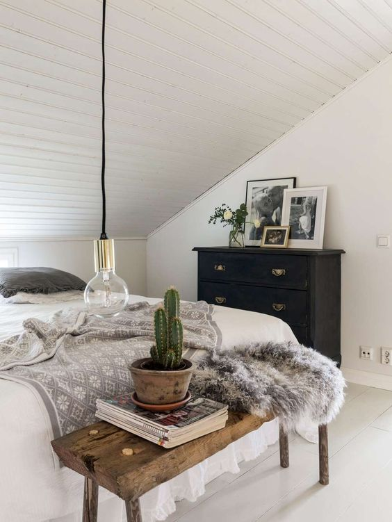 a small attic Nordic bedroom with a bed, a wooden bench, a black dresser, black and white artworks and a potted cactus