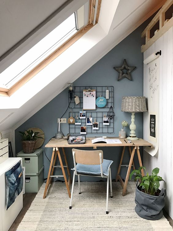a small attic home office with a trestle desk, a vintage chair, a small cabinet and boxes for storage plus a grid with photos