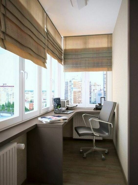 a small balcony home office with a built-in desk, a comfy chair, shades and everything necessary is a great idea