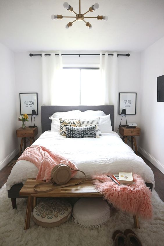 a small boho bedroom with a grey upholstered bed, neutral and printed bedding, pink touches and mid-century modern furniture