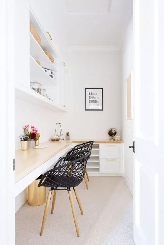a small contemporary home office with a shared desk, a couple of chairs, a large storage unit with closed and open compartments