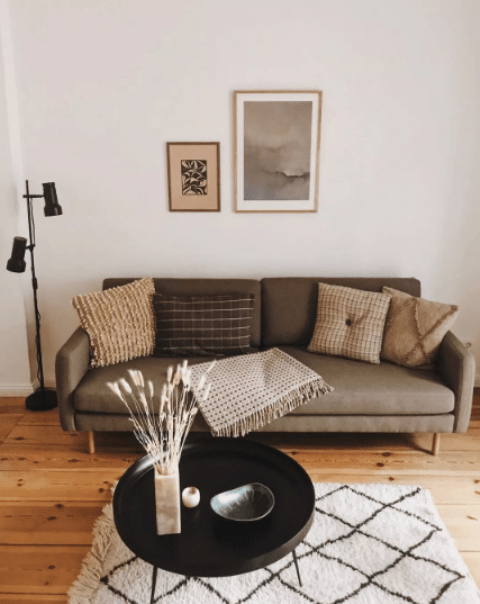 a small earthy-toned Scandi living room with a green sofa and a mix of pillows, a black table, artworks and a black floor lamp