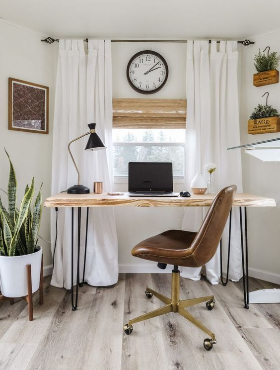 a small farmhouse home office with a desk with hairpin legs, a leather chair, neutral curtains, potted greenery and a clocj is very welcoming