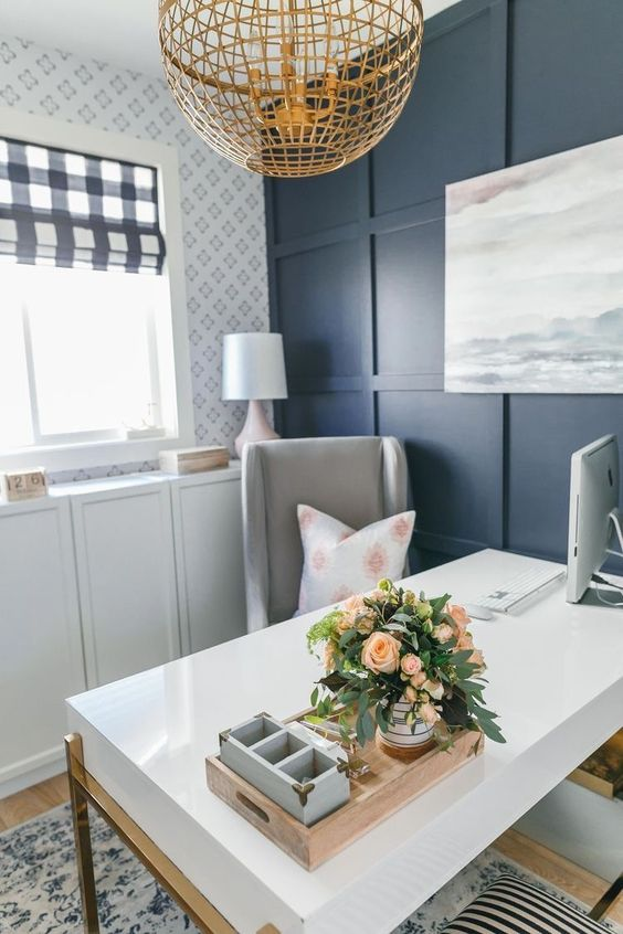 a small farmhouse home office with blue paneling on the wall, printed wallpaper, a chic desk, a grey chair and a wicker lamp is lovely