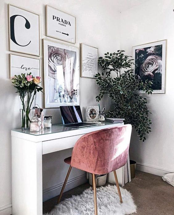 a small girlish home office with a sleek desk, a pink chair, some rugs and a beautiful gallery wall for inspiration