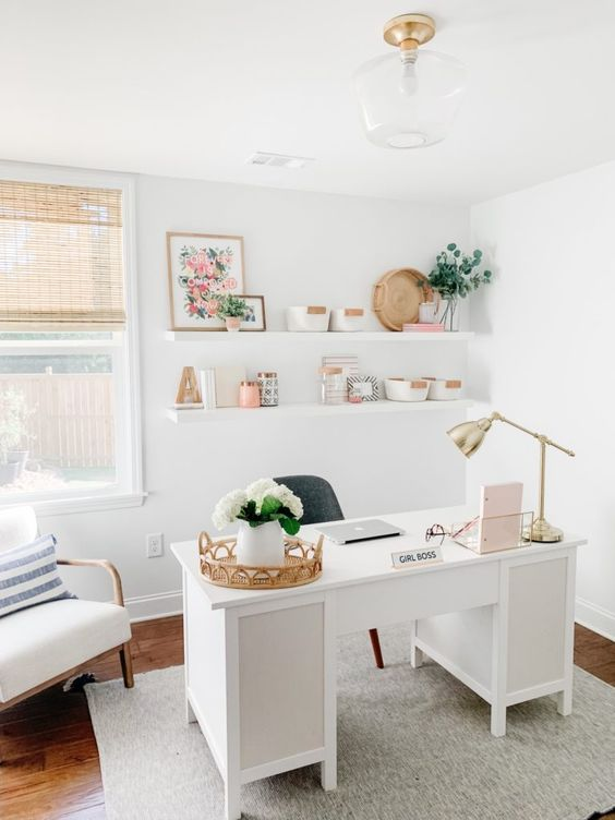 a small light-filled home office with a vintage desk, open shelves, woven shades, a comfy chair and some decor on the shelves