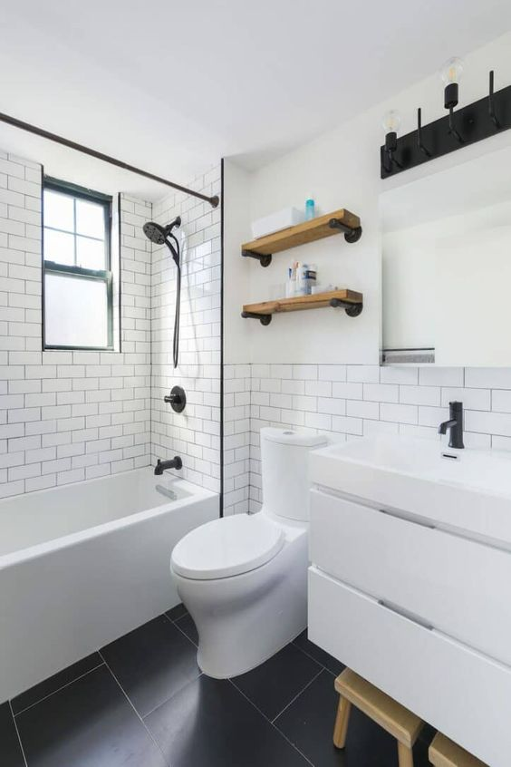a small minimalist bathroom with white subway tiles, a white vanity, open shelves and touches of black to make the space look contrasting
